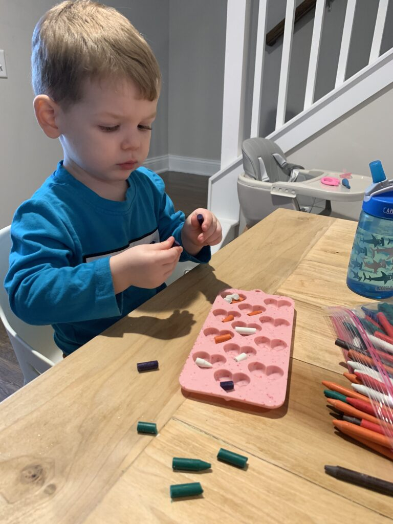 toddler breaking crayons for mold