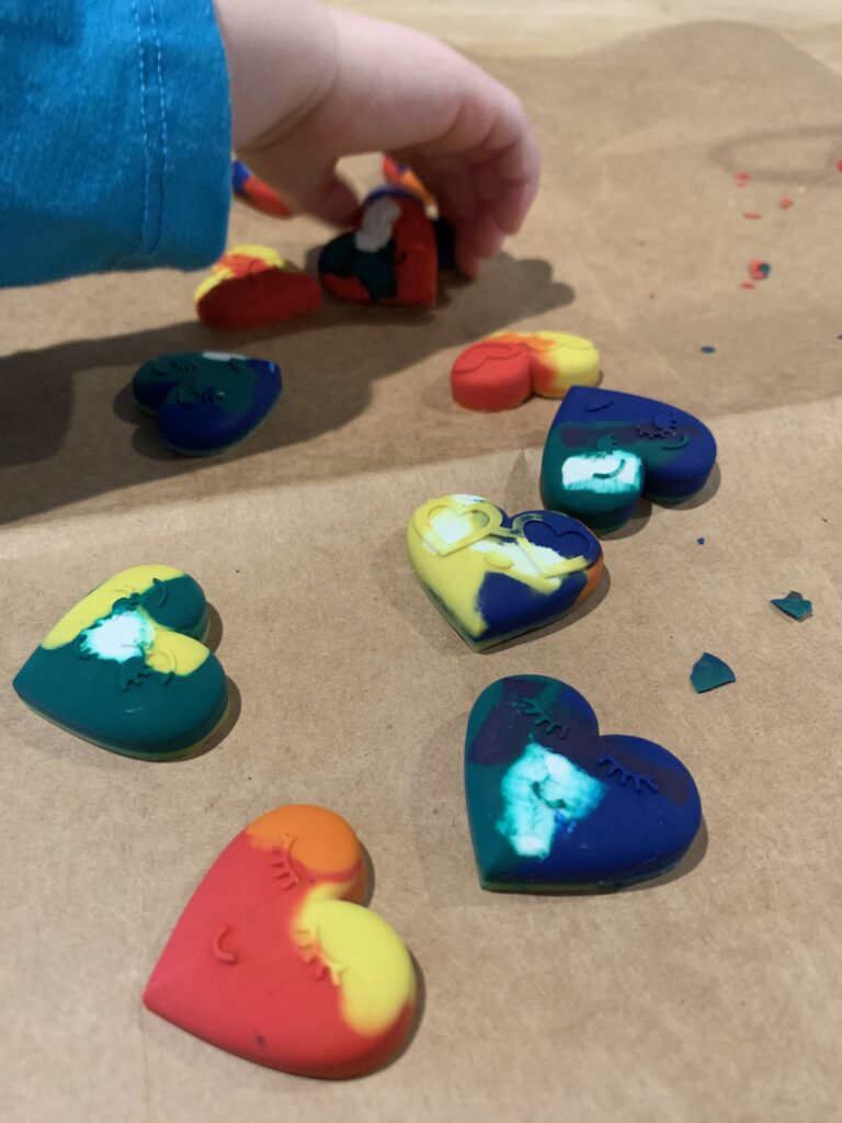 toddler hand picking up heart shaped crayons