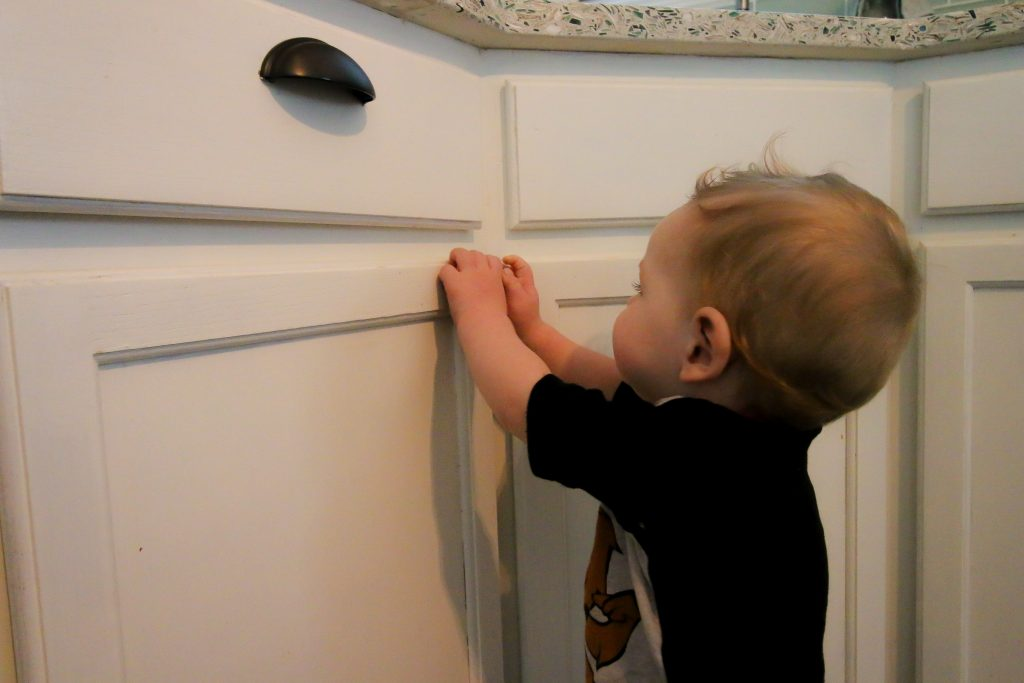 baby trying to unlock cabinet