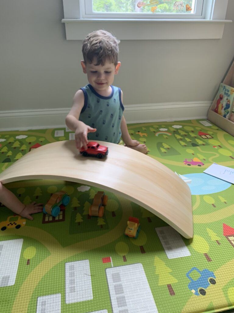 using a wobble board as a bridge or ramp with toy cars