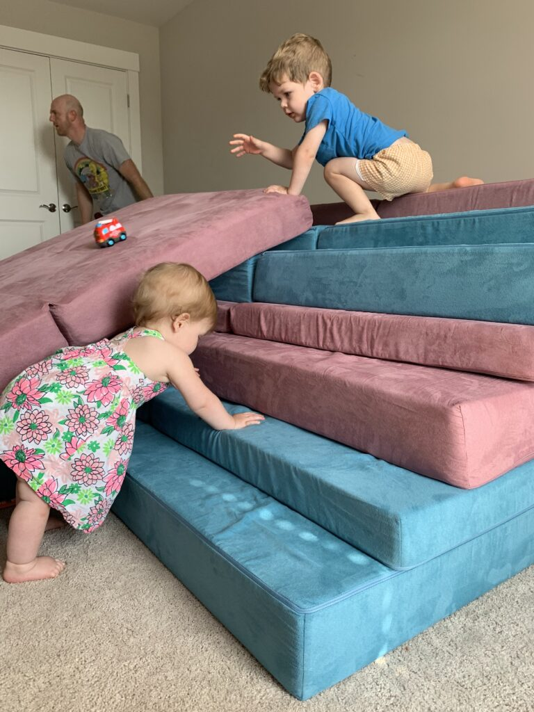 baby crawling up nugget steps