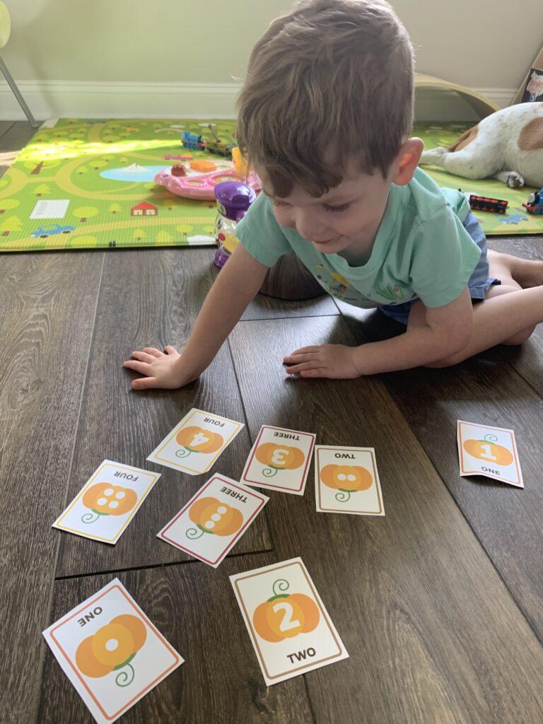 toddler playing with Fall memory matching game - free printable!